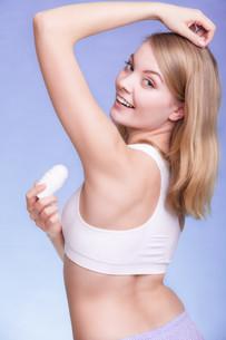 girl applying deodorant stick in the armpit. skin careの写真素材 [FYI00770505]