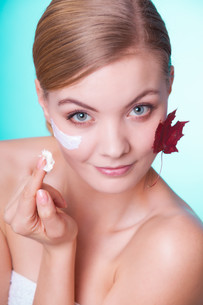 skin care. face of young woman girl with red maple leaf.の写真素材 [FYI00770527]