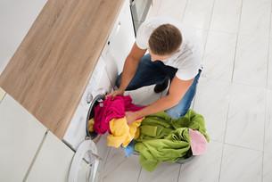 Man Putting Clothes In Washing Machineの写真素材 [FYI00770544]