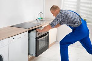 Repairman Repairing Ovenの写真素材 [FYI00770545]