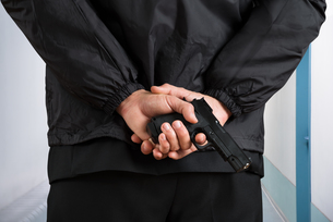 Close-up Of Bodyguard Holding Pistolの写真素材 [FYI00770554]