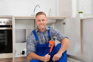 Plumber With Adjustable Wrench In Kitchen Roomの写真素材 [FYI00770561]