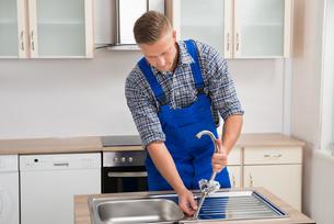 Repairman Installing Faucet Of Kitchen Sinkの写真素材 [FYI00770565]