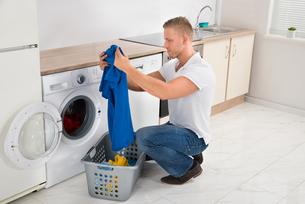 Man With T-shirt While Using Washing Machineの写真素材 [FYI00770572]