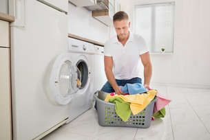 Man Putting Colorful Towels Into The Washing Machineの写真素材 [FYI00770586]