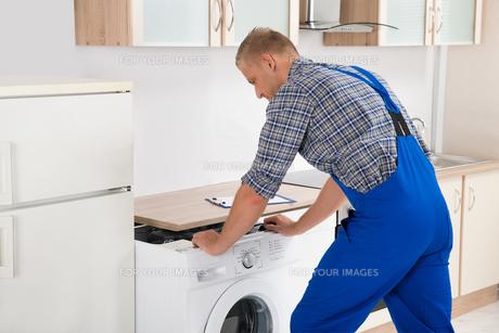 Worker Repairing Washerの写真素材 [FYI00770592]