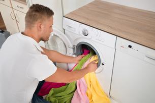 Man Loading Towels Into The Washing Machineの写真素材 [FYI00770608]