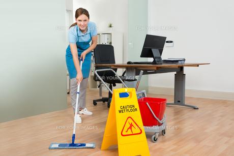 Female Janitor Cleaning Hardwood Floor In Officeの写真素材 [FYI00770616]