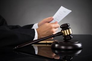Judge Holding Document At Deskの写真素材 [FYI00770617]