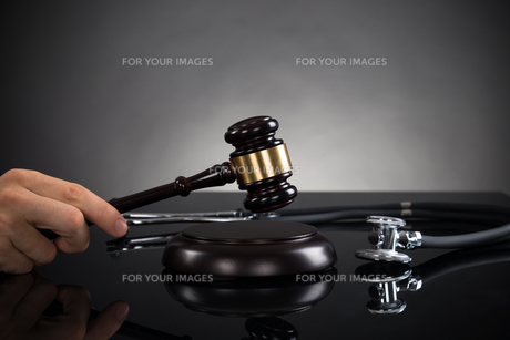 Close-up Of Hands With Gavel And Stethoscopeの写真素材 [FYI00770634]