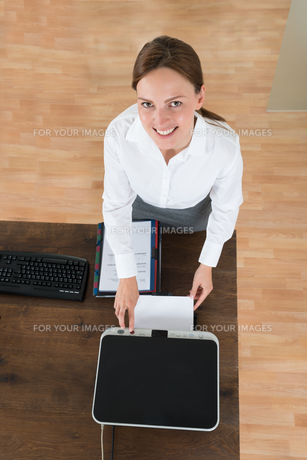 Young Businesswoman Using Printer In Officeの写真素材 [FYI00770645]