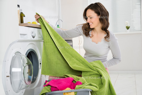 Woman Laundering Clothes In Washerの写真素材 [FYI00770740]