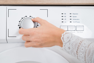 Person Hands Turning Button Of Washing Machineの写真素材 [FYI00770742]