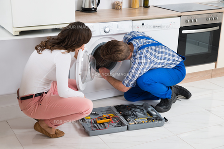 Repairman Repairing Washer In Front Of Womanの写真素材 [FYI00770761]