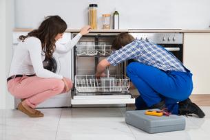 Woman Looking At Repairman Repairing Dishwasherの写真素材 [FYI00770765]