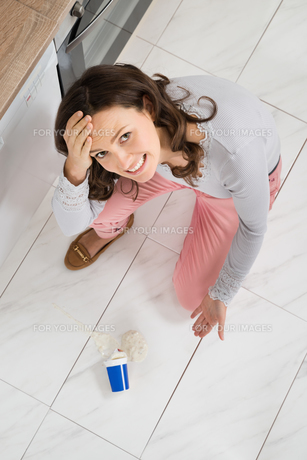 Woman Looking At Yoghurt Spilled On The Floorの写真素材 [FYI00770786]