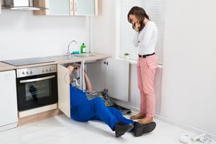 Repairman Repairing Pipe While Woman In The Kitchenの写真素材 [FYI00770794]