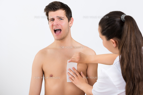 Beautician Waxing Man's Chest In Beauty Centerの写真素材 [FYI00770817]
