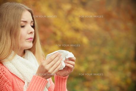 sick ill woman in autumn park sneezing in tissue.の素材 [FYI00771161]
