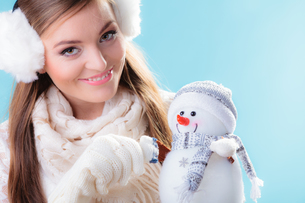 woman in warm clothes holding toy snowman.の写真素材 [FYI00771169]