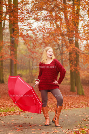smiling happy fashion woman cute girl in a maroon sweater with umbrella relaxing in fall autumn park. happiness and relax in forest.の写真素材 [FYI00771171]