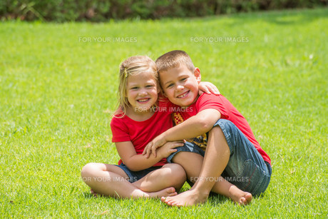 Brother ans Sister in Red on Lawnの写真素材 [FYI00771346]