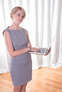 Portrait attractive young business woman with laptopの写真素材 [FYI00771447]
