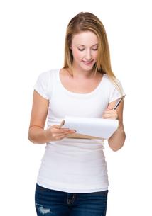 Caucasian woman take note on clipboardの写真素材 [FYI00771526]