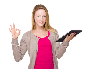 Caucasian woman with tablet and ok sign gestureの写真素材 [FYI00771562]
