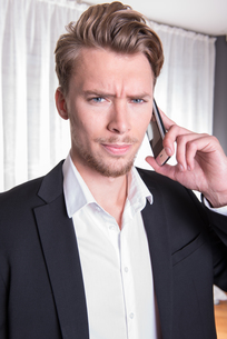portrait angry young business man in suit on the phoneの素材 [FYI00771956]
