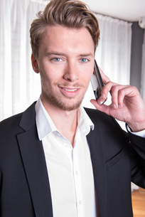 Portrait young business man in suit on the phoneの素材 [FYI00771964]