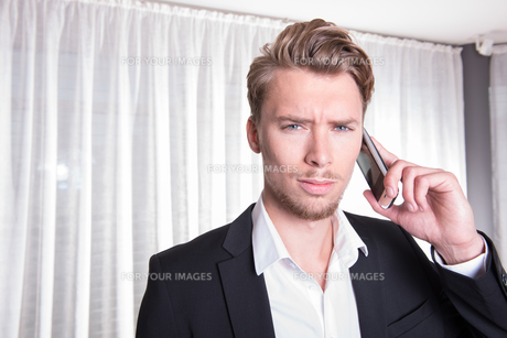 portrait angry young business man in suit on the phoneの素材 [FYI00771971]
