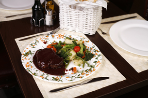 Elegant restaurant plate with a big steak and gravy garnished with steamed vegetables.の写真素材 [FYI00771998]