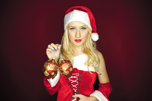 Sexy Christmas girl with tree ornaments on red backgroundの写真素材 [FYI00772013]