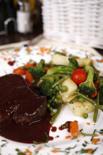 Elegant restaurant plate with a big steak and gravy garnished with steamed vegetables.の写真素材 [FYI00772020]