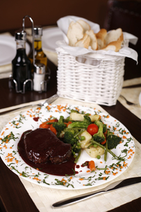 Elegant restaurant plate with a big steak and gravy garnished with steamed vegetables.の写真素材 [FYI00772044]