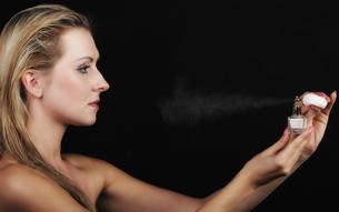 portrait of beautiful woman spraying perfume on blackの写真素材 [FYI00772277]