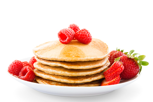 Plate full of pancakes with berries over white backgroundの写真素材 [FYI00772389]