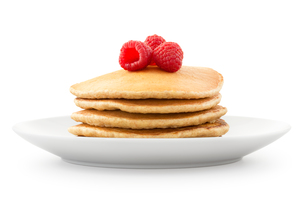Plate full of pancakes with berries over white backgroundの写真素材 [FYI00772405]