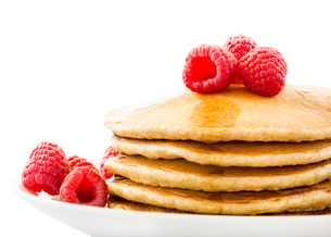 Plate full of pancakes with berries over white backgroundの写真素材 [FYI00772419]