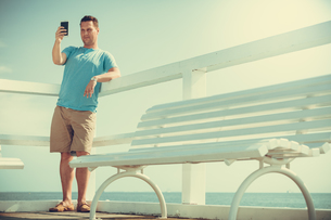 man tourist on pier taking selfie with smartphone.の写真素材 [FYI00772484]