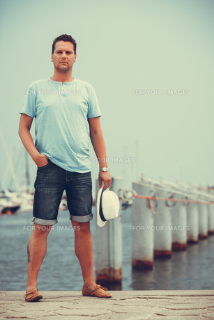 fashion handsome man on a pier in the harbor with yachts.の素材 [FYI00772488]