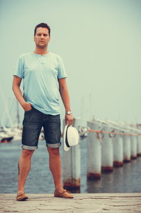 fashion handsome man on a pier in the harbor with yachts.の写真素材 [FYI00772488]