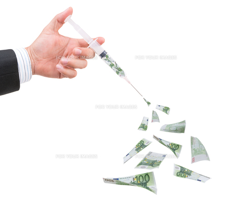 hand holding syringe filled with currencyの写真素材 [FYI00772748]