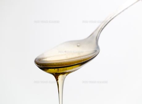 Spoon with liquid honey,Spoon with liquid honey,Spoon with liquid honey,Spoon with liquid honeyの写真素材 [FYI00773335]