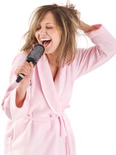 Woman singing with hairbrush,Woman singing with hairbrushの写真素材 [FYI00773473]