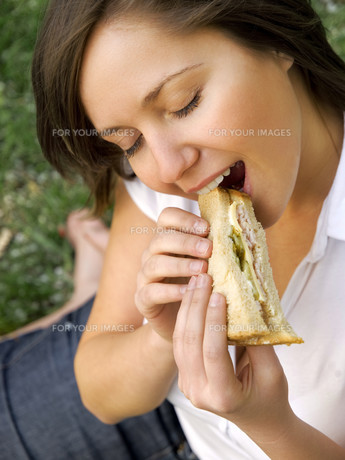Young woman eating sandwich outdoors,Young woman eating sandwich outdoorsの写真素材 [FYI00773511]