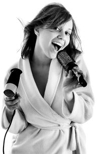 Woman singing with hairbrush,Woman singing with hairbrushの写真素材 [FYI00773638]