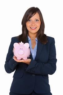 Businesswoman holding pig money-boxの写真素材 [FYI00773654]