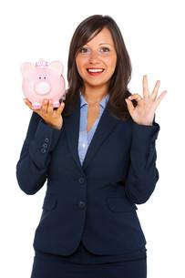 Businesswoman holding pig money-boxの写真素材 [FYI00773664]